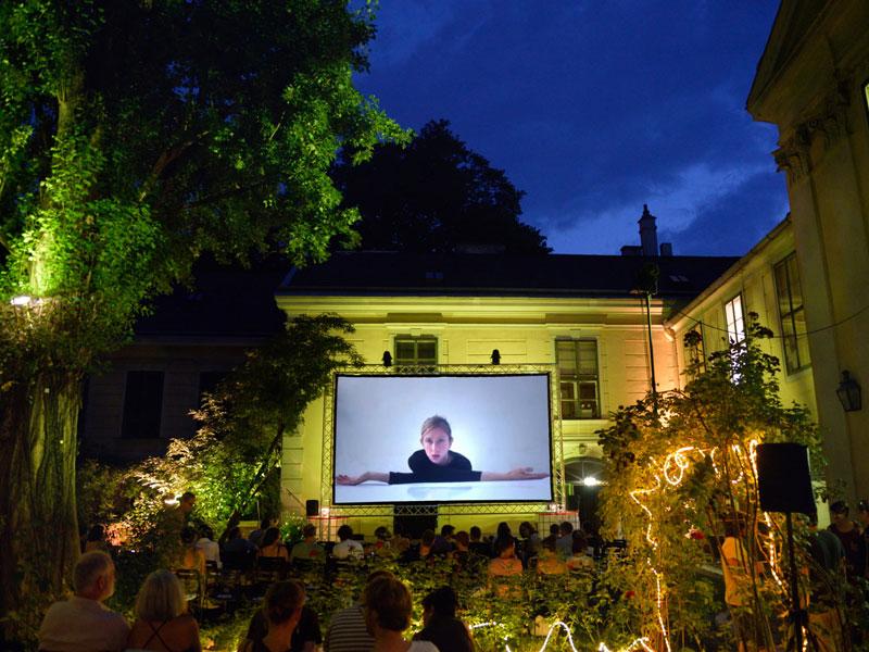 Menschen sehen im Garten des Volkskundemuseums einen Film
