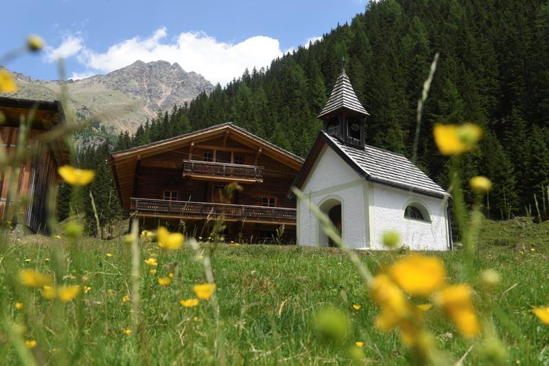 Ober- und Unterstalleralm Bild 8: Kapelle und Hütte im Hintergrund mit Bergen und im Vordergrund Blumen
