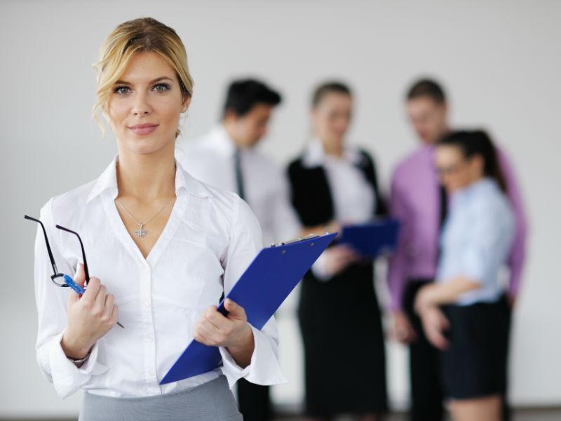 Businessfrau steht im Vordergrund vor Mitarbeitern