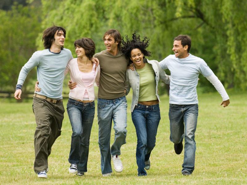 Freunde laufen gemeinsam über eine Wiese