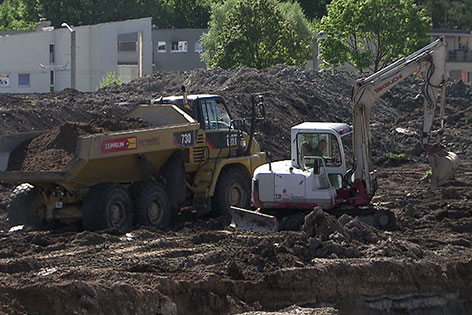 Baufahrzeuge tragen Boden ab auf Baustelle