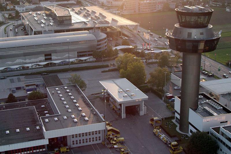 Tower und Gebäude des Flughafens Salzburg (Airport) aus der Luft im Abendlicht