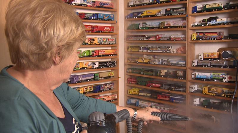 Frau reinigt Modell-LKW Sammlung