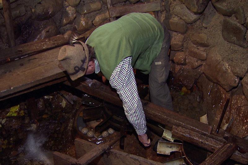 Mann öffnet Mahlwerk eine Kugelmühle im Teufelsgraben bei Seeham