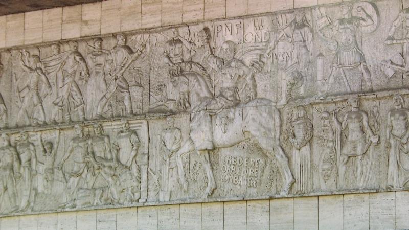 """Detail aus dem Mussolini-Relief ohne Verhüllung, mit dem Duce hoch zu Ross, darunter der Spruch """"credere, obbedire, combattere"""""""