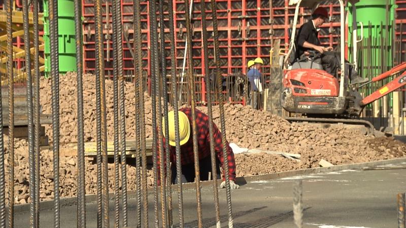 Arbeiter auf Baustelle, im Hintergrund Bagger