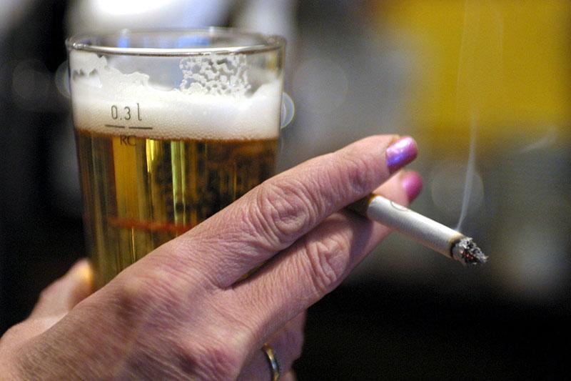 Hand hält kleines Bier und Zigarette