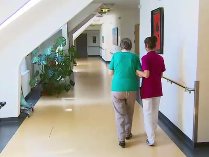 Pflegerin mit Frau in Seniorenheim