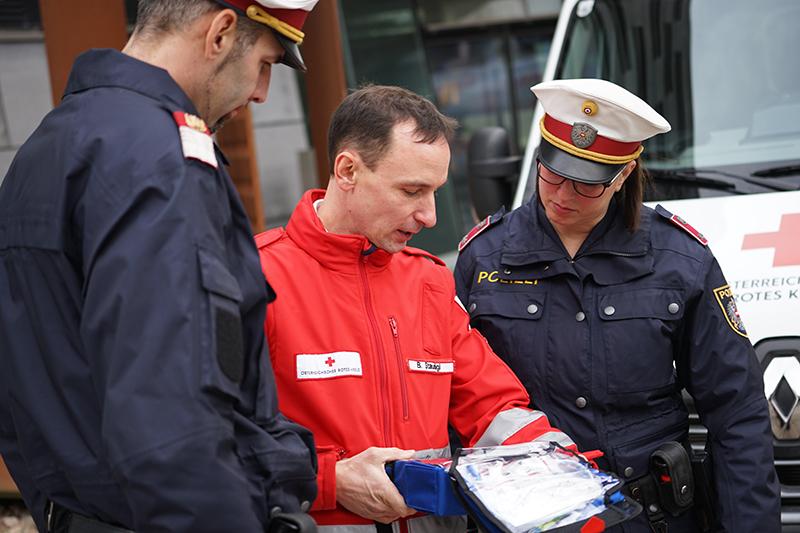 Sanitäter zeigt Polizisten Defibrillator