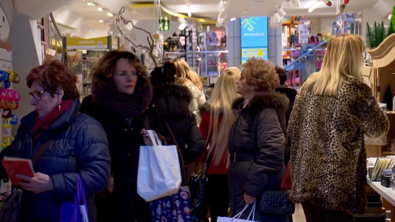 Geschäft, in dem sich Kundinnen mit Einkaufstaschen drängen