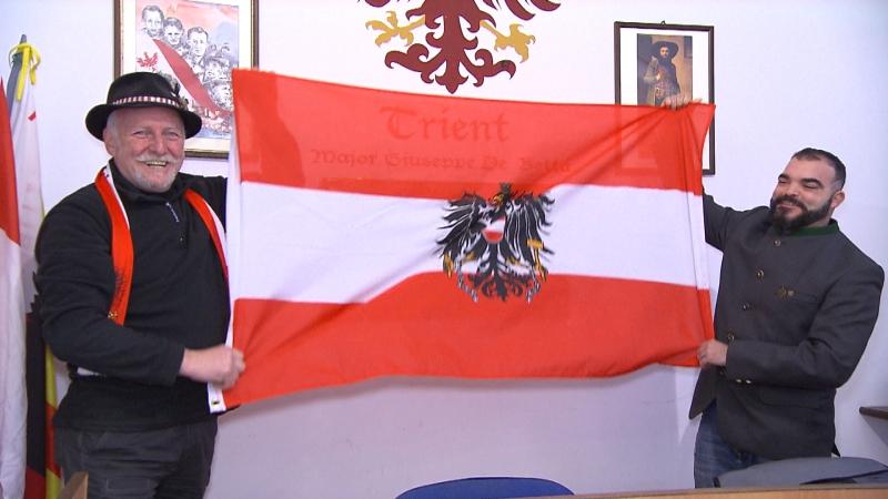 Trentiner Schützen zeigen lachend die österreichische Flagge mit dem Bundesadler