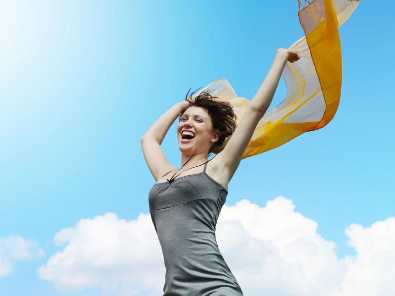 Frau streckt freudig Arme in die Höhe