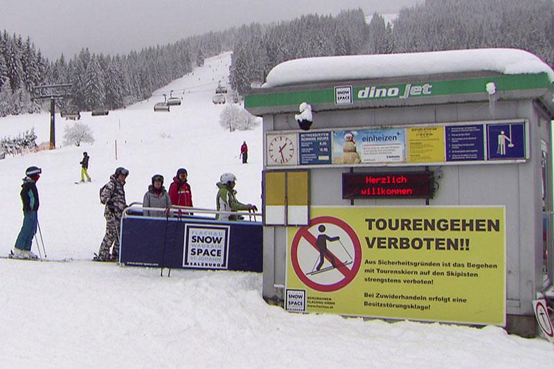 Verbotsschild für Skitourengeher auf Piste bei Seilbahn-Talstation in Flachau
