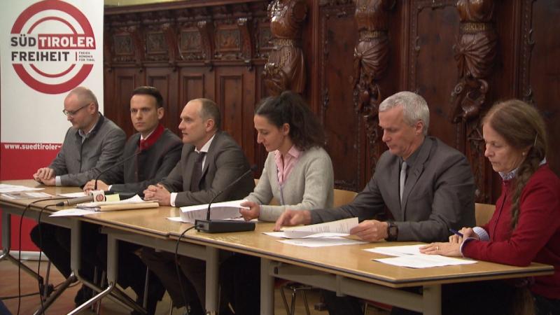 Vertreter der Süd-Tiroler Freiheit bei der Medienkonferenz an einem Tisch mit Parteizeichen im Hintergrund