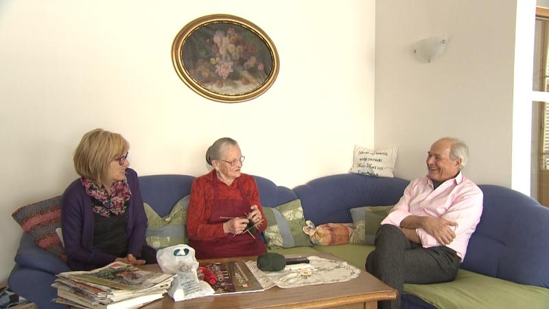 Reinhard Zingerle im Gespräch mit zwei Frauen von Fam. Pfeifer auf Sofa, eine Frau strickt Socken