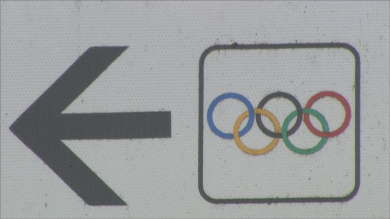 Verkehrsschild mit olympischen Ringen und Pfeil nach links