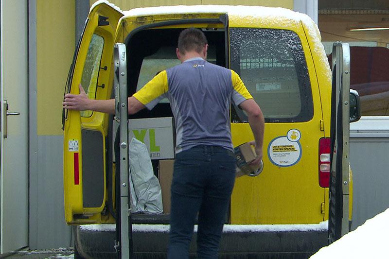 Zusteller der Post mit Postfahrzeug (Briefträger)