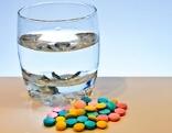 Tabletten und Wasserglas