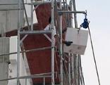 Bauarbeiter mit Polystyrol Kunststoff Dämmplatten auf Gerüst einer Baustelle