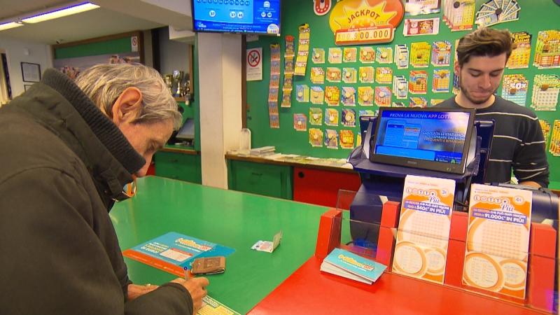 Ein Mann füllt in der Lottoannahmestelle seinen Schein aus, im Hintergrund ist der Jackpot zu sehen: 100.900.000 Euro