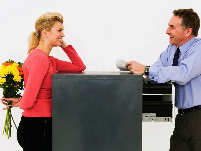 Frau und Mann unterhalten sich vor einem Büromöbel, sie hat Blumen in der Hand