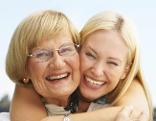 Junge Frau umarmt ältere Frau