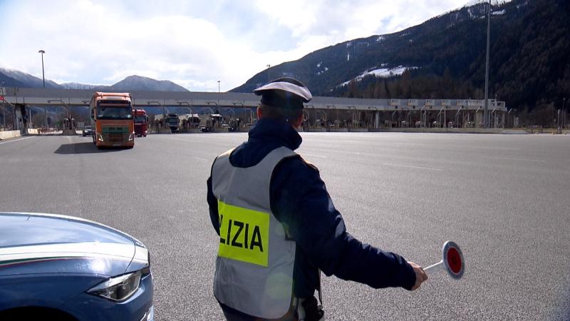 Polizist hält mit der Kelle einen Lkw an der Mautstelle Sterzing auf