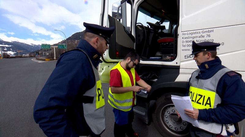 Polizisten überprüfen die Papiere eines Lkw-Fahrers, der neben seinem Fahrzeug steht