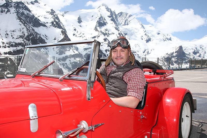 Rudi Roubinek in Oldtimer Cabrio auf der Franz Josefs Höhe an der Großglockner Hochalpenstraße mit Blick auf den Glockner