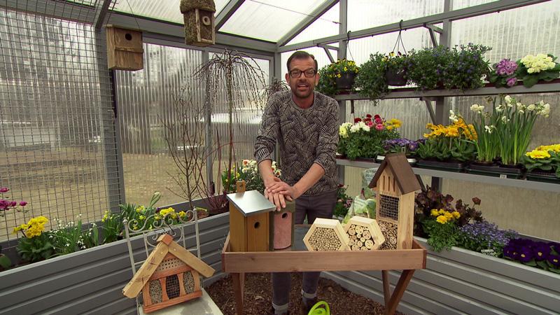 Karl Ploberger im Gewächshaus mit Nistkästen und Insektenhotels