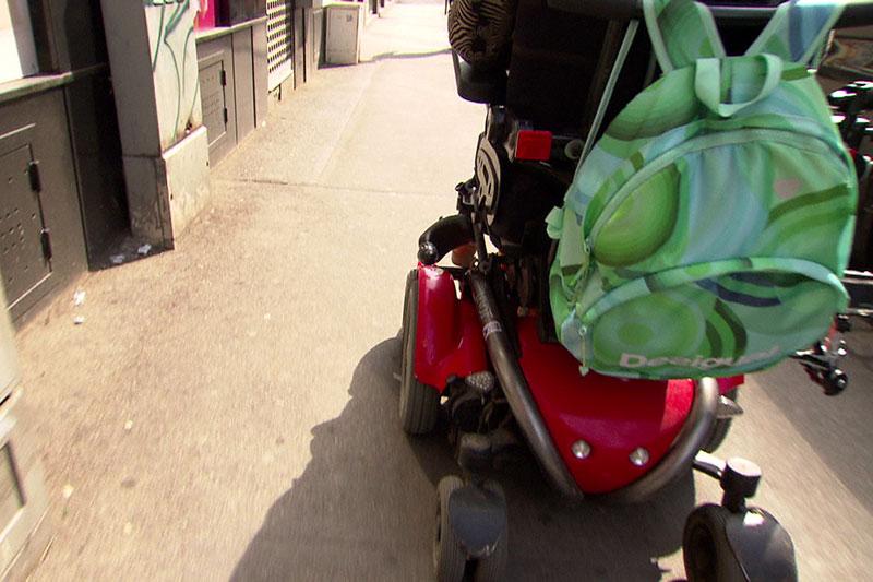 Rollstuhlfahrer in Elektrorollstuhl auf Gehsteig