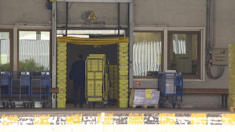 Verteilungszentrum von außen, Mann bringt Schachteln auf Wagen ins Innere