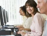 Frau sitzt lächelnd vor Computer