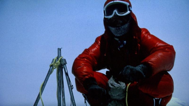 Reinhold Messner ohne Sauerstoff am Gipfel des Mount Everest, in rotem Skianzug und Gesichtsmaske fast nicht zu erkennen
