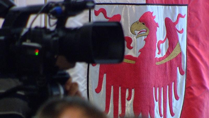 Kamera, dahinter Südtiroler Fahne mit Adler