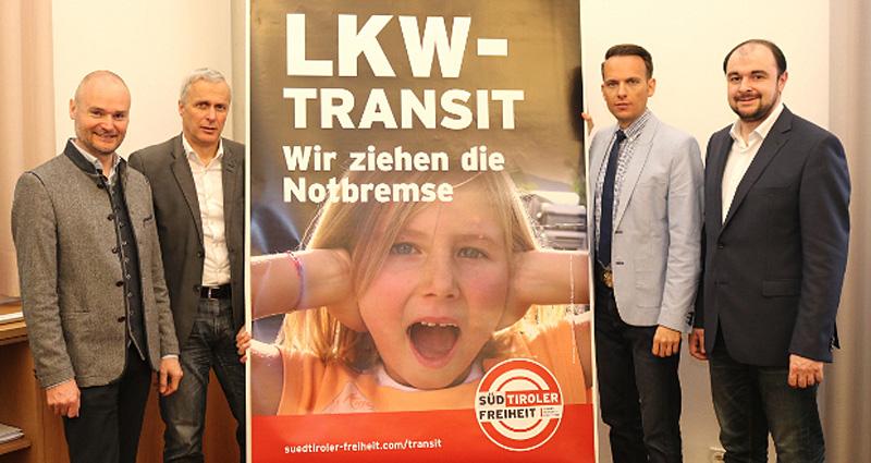 """Vorstellung des Werbeplakats LKW-Transit - Wir ziehen die Notbremse der Bewegung """"Süd-Tiroler Freiheit"""", Parteivertreter stehen neben dem Plakat"""
