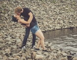 Mann und Frau kuessen sich an einem Steinstrand