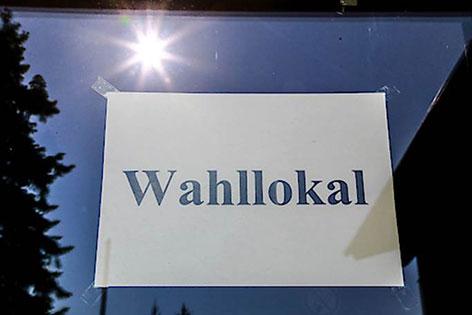 """Sonne spiegelt sich in Scheibe mit Zettel """"Wahllokal"""""""