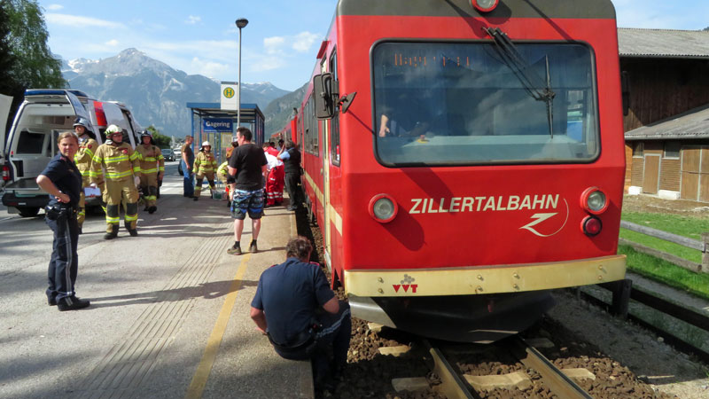 Zillertalbahn, ein Polizist begutachtet die Bahn, Passanten und Rettungskräfte