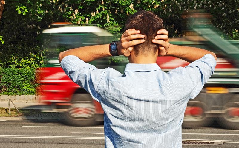 Mann hält sich die Ohren auf Straße zu