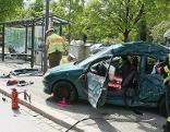 Zerstörtes Auto bei Bushaltestelle