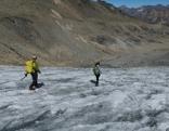 Zwei Leute wandern über Gletscherzunge, links und rechts ist der Gletscher aper