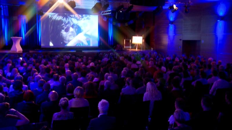 Voller Saal bei der Filmpremiere, an der Leinwand ein Bild vom jungen Reinhold Messner