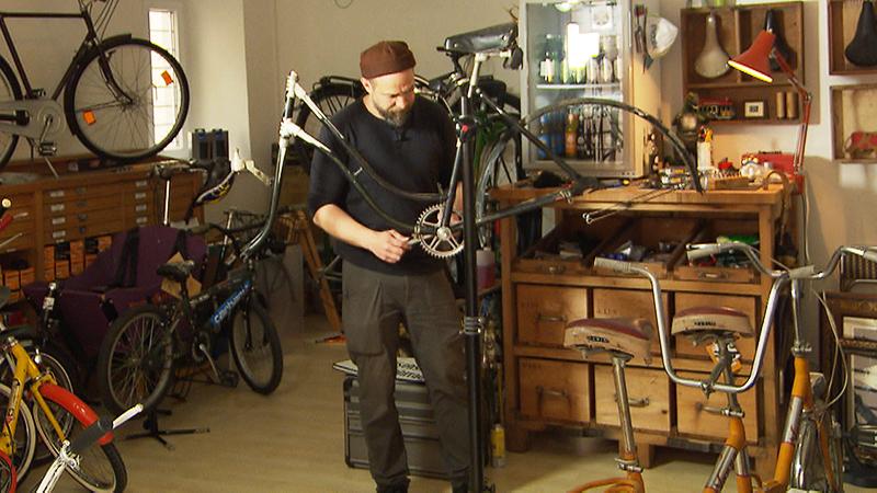 Albart Chmelar hantiert an altem Fahrrad