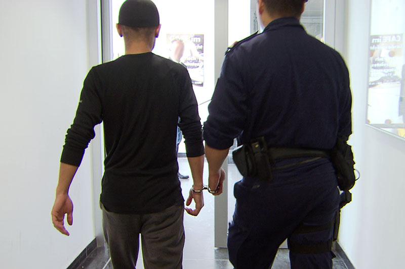 Verdächtiger wird von Polizisten an Handschelle auf Gang geführt