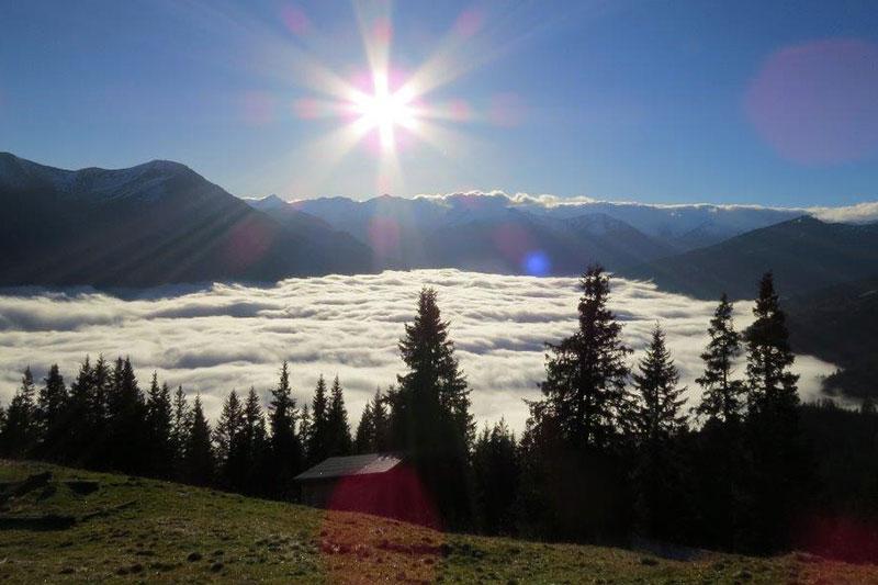 Panorama mit Sonne und Nebel im Tal
