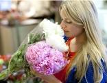 Frau riecht an Blumenstrauss