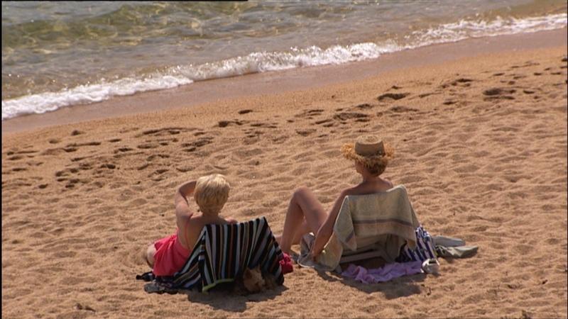 Mann und Frau liegen am Sandstrand, vor ihnen das Meer, von hinten gefilmt