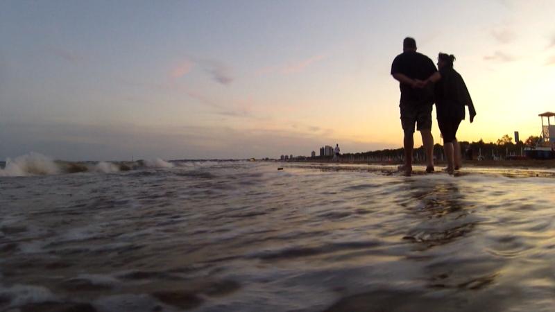 Zwei Spaziergänger am Sandstrand, gehen im Wasser bei Sonnenuntergang
