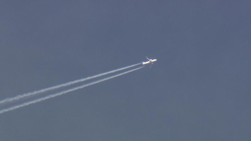Flugzeug im blauen Himmel mit Kondensstreifen